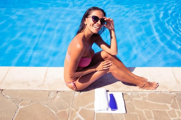 Portret wesołej kobiety w okularach przeciwsłonecznych opalającej się w pobliżu basenu na świeżym powietrzu