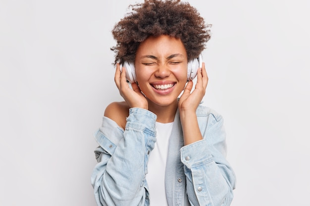 Portret wesołej kobiety z włosami afro trzyma ręce na słuchawkach stereo, ma zamknięte oczy, uśmiecha się szeroko, pokazuje białe zęby, cieszy się przyjemną muzyką na białym tle nad białą ścianą