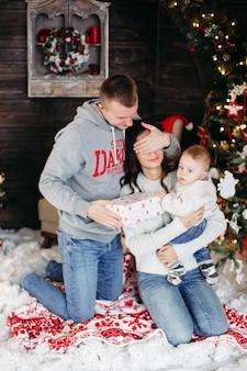 Portret wesołej kochającej rodziny rozpakowującej prezenty świąteczne z dziećmi przy udekorowanym kominku i choince