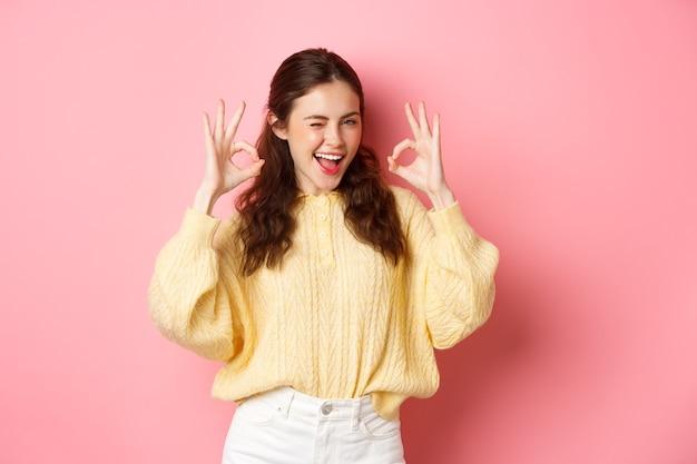 Portret wesołej ładnej dziewczyny mrugającej i mówiącej `` tak '', pokazująca znak w porządku, w porządku gest, chwała dobrą robotę, dobra robota, stojąca zadowolona na różowej ścianie