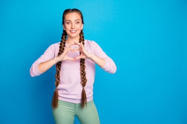 Portret wesołej, marzycielskiej dziewczyny tysiącletniej pokaż symbol miłości zrób serce z palcami data ukochany chłopak poczuj zadowolenie wyrażenie nosić młodzież zielone spodnie spodnie izolowany niebieski kolor tło