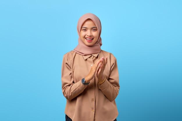Portret wesołej młodej azjatyckiej kobiety gestykulującej brawa, gratulacje na niebieskim tle