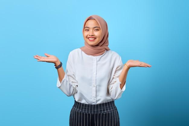 Portret wesołej młodej azjatyckiej kobiety trzymającej rękę prezentującą reklamy na niebieskim tle