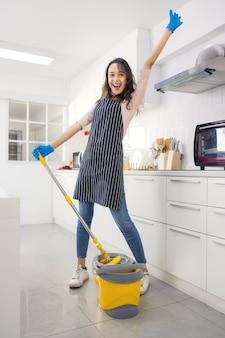 Portret wesołej młodej gospodyni domowej trzymającej środki czystości