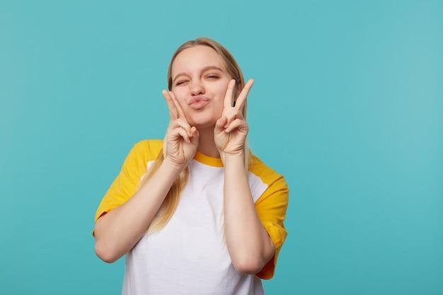 Portret wesołej młodej jasnowłosej kobiety, która wydyma usta i mruga do kamery, podnosząc rękę z gestem pokoju, pozując na niebieskim tle