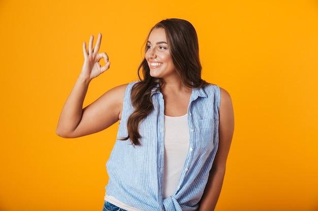 Portret wesołej młodej kobiety dorywczo, pokazując gest ok