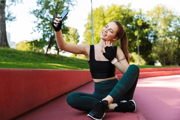 Portret wesołej młodej kobiety noszącej dres biorący selfie na smartfonie siedząc na boisku sportowym podczas treningu w zielonym parku