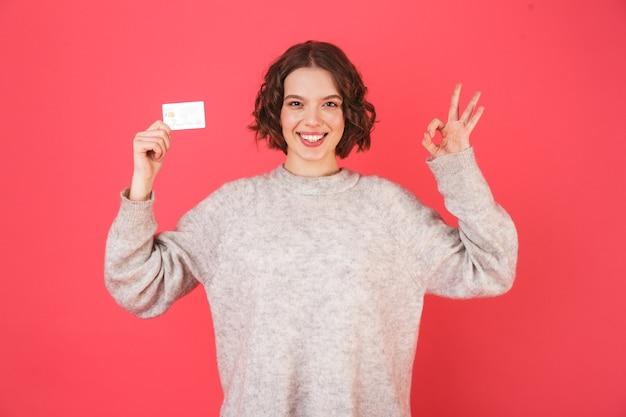 Portret wesołej młodej kobiety stojącej na białym tle nad różem, prezentując plastikową kartę kredytową