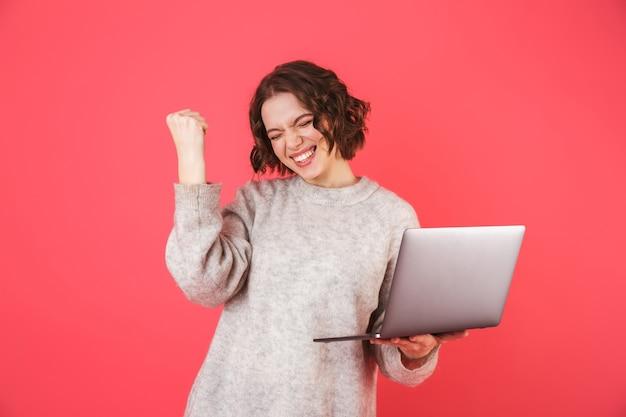 Portret wesołej młodej kobiety stojącej na białym tle nad różowym, pracującej na komputerze przenośnym, świętuje sukces