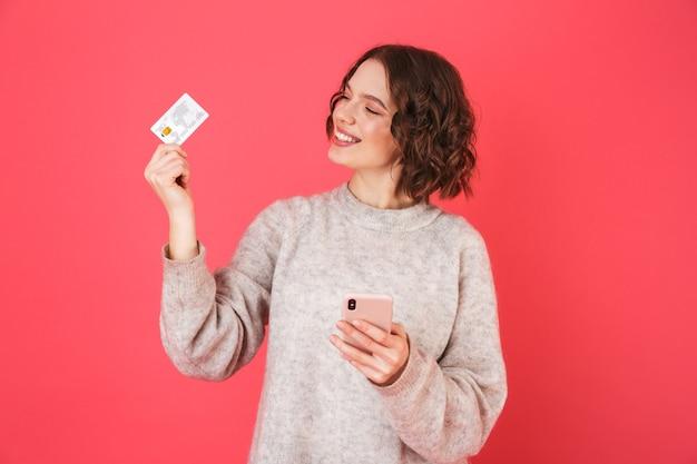 Portret wesołej młodej kobiety stojącej na białym tle nad różowym, przy użyciu telefonu komórkowego, pokazując plastikową kartę kredytową