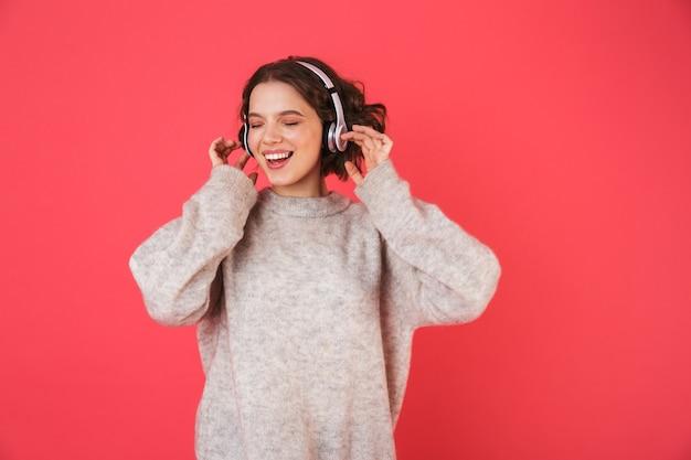 Portret wesołej młodej kobiety stojącej na białym tle nad różowym, słuchanie muzyki w słuchawkach, taniec