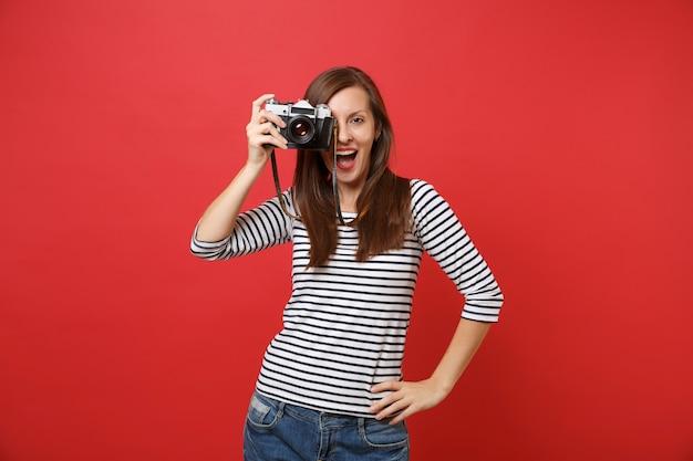 Portret wesołej młodej kobiety w pasiastych ubraniach robiącej zdjęcie na retro vintage aparat fotograficzny