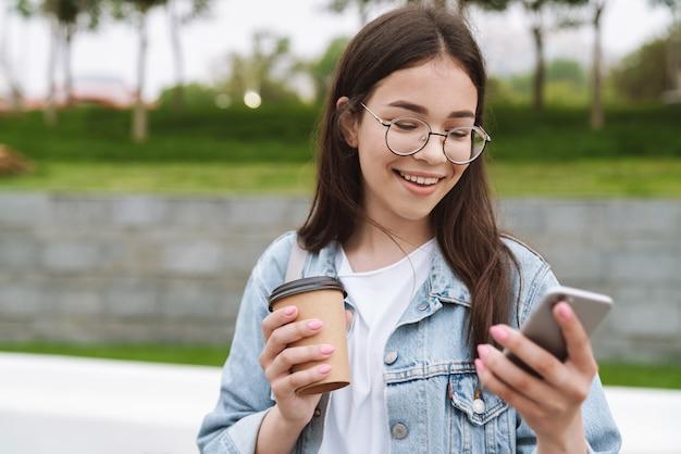 Portret wesołej młodej ładnej studentki spacerującej na świeżym powietrzu w zielonym parku przyrody pijącej kawę za pomocą telefonu komórkowego na czacie