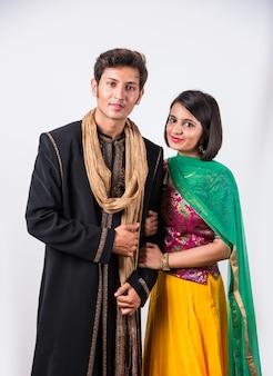 Portret wesołej młodej pary indyjskiej w tradycyjnym stroju w diwali