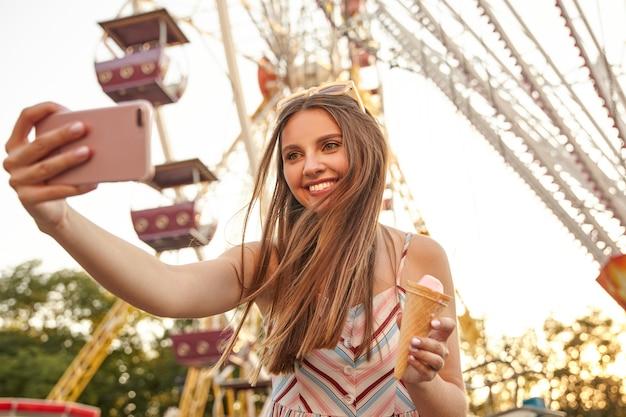 Portret wesołej młodej uroczej damy z uroczym uśmiechem pozuje nad atrakcjami w wesołym miasteczku, robi sobie zdjęcie smartfonem, trzymając w ręku lody w rożku