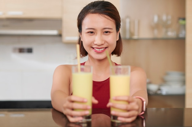 Portret wesołej młodej wietnamki trzymającej dwie szklanki koktajlu proteinowego o smaku bananowym