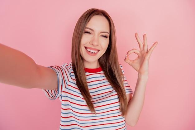 Portret wesołej niezawodnej doradczyni sprawia, że selfie pokazuje znak okey na różowym tle