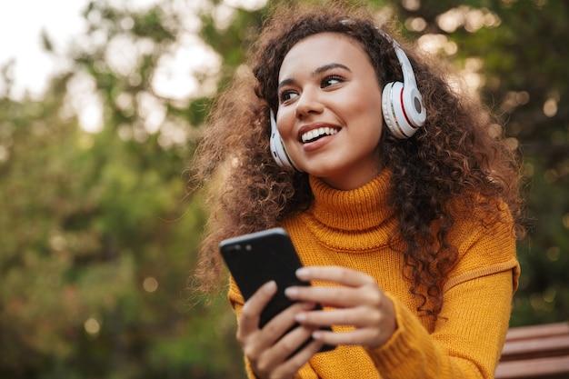 Portret wesołej optymistycznej pięknej młodej kręconej kobiety siedzieć na ławce w parku na zewnątrz, słuchając muzyki w słuchawkach przy użyciu telefonu komórkowego.