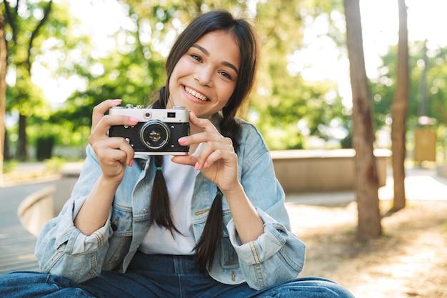 Portret wesołej optymistycznej słodkiej młodej studentki w okularach, siedzącej na ławce na zewnątrz w parku przyrody, trzymającej aparat