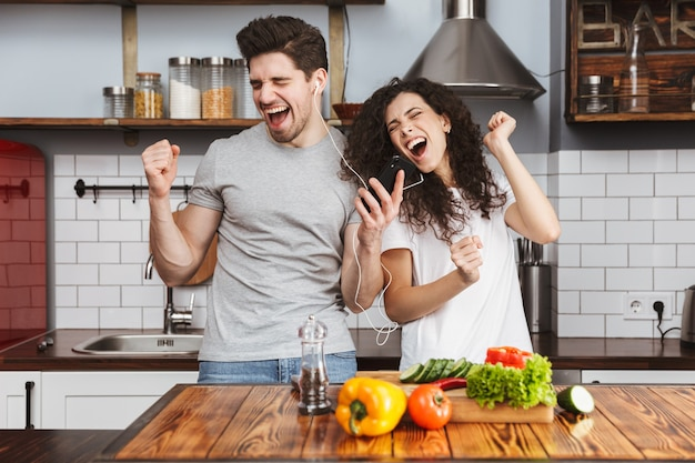 Portret wesołej pary mężczyzny i kobiety podczas wspólnego słuchania muzyki podczas gotowania salat w kuchni w domu