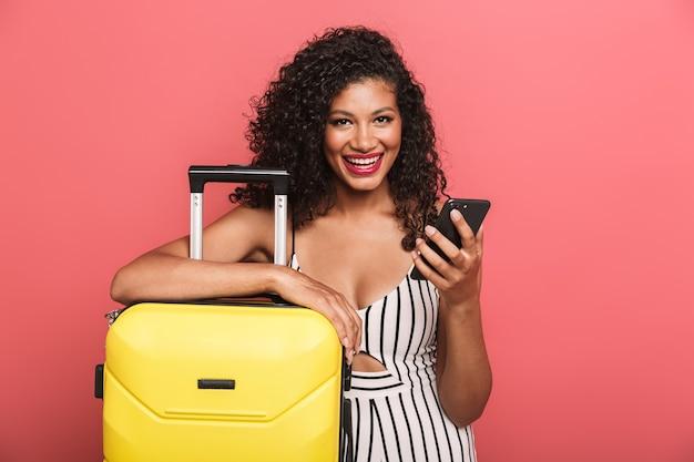 Portret wesołej pięknej młodej kobiety w letniej odzieży stojącej z walizką odizolowaną na różowej ścianie, trzymającej telefon komórkowy