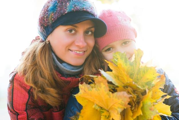 Portret wesołej pięknej młodej matki z ładną córką trzymającą w rękach jesienne żółte liście klonu podczas spaceru po parku. koncepcja więzi rodzinnych i tradycji