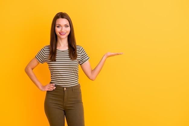 Portret wesołej pozytywnej dziewczyny promotora trzymaj rękę wybierz sugeruj promocję obecne reklamy noszą dobrze wyglądające ubrania odizolowane na żywej kolorowej ścianie