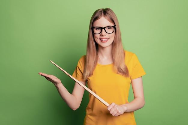 Portret wesołej pozytywnej, niezawodnej odpowiedzialnej nauczycielki, pani trzyma wskaźnik, nosi okulary, żółtą koszulkę