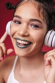 Portret wesołej punkowej dziewczyny z dziwaczną fryzurą i ciemną szminką, uśmiechającą się podczas słuchania muzyki przez słuchawki izolowane nad czerwoną ścianą