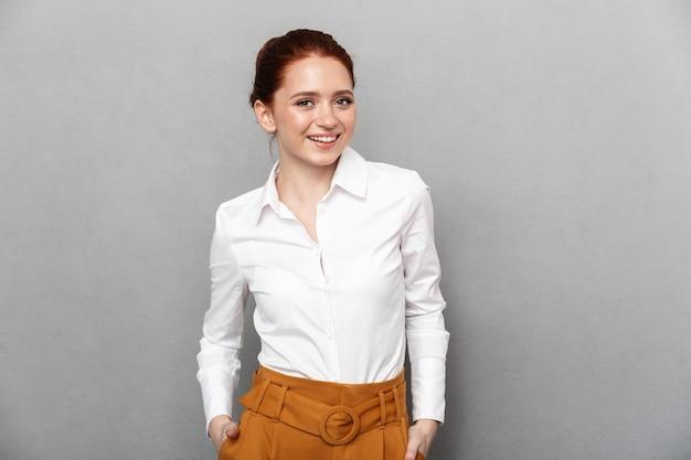 Portret wesołej, rudej bizneswoman 20s w formalnym stroju, uśmiechniętej i pozującej w biurze na białym tle nad szarym