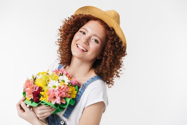 Portret wesołej rudej kręconej kobiety 20 lat w letnim słomkowym kapeluszu uśmiecha się i trzyma pudełko na kwiaty izolowane nad białą ścianą