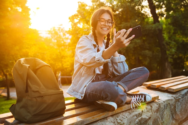 Portret wesołej ślicznej młodej studentki w okularach, siedzącej na ławce na zewnątrz w parku przyrody z pięknym światłem słonecznym za pomocą telefonu komórkowego, rozmawiając, weź selfie