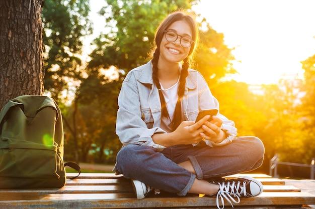 Portret wesołej ślicznej młodej studentki w okularach siedzącej na ławce na zewnątrz w parku przyrody z pięknym światłem słonecznym za pomocą telefonu komórkowego