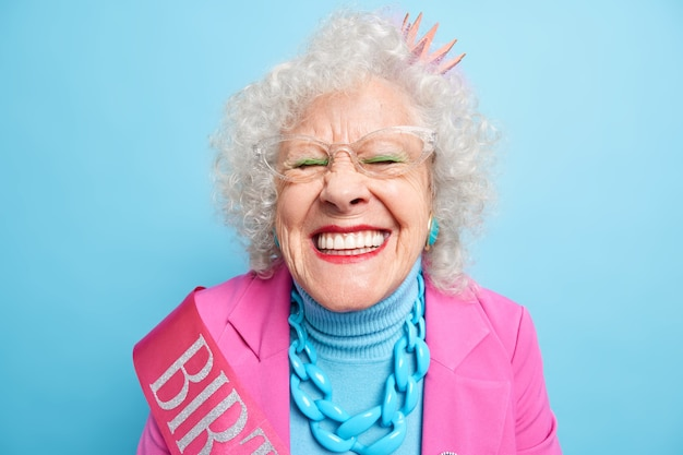 Portret wesołej starszej kobiety chichocze, zamyka oczy, uśmiecha się szeroko, ma białe idealne zęby lubi spędzać wolny czas na imprezie świętuje specjalną okazję. koncepcja wieku emerytalnego kobiet