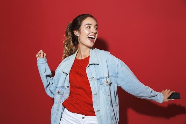 Portret wesołej stylowej młodej kobiety w dżinsowej kurtce stojącej na białym tle nad czerwoną ścianą, słuchającej muzyki przez bezprzewodowe słuchawki, śpiewającej