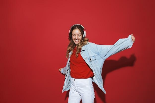 Portret wesołej stylowej młodej kobiety w dżinsowej kurtce stojącej na białym tle nad czerwoną ścianą, słuchającej muzyki przez słuchawki, tańczącej
