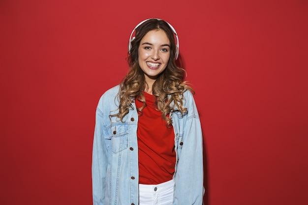 Portret wesołej stylowej młodej kobiety w dżinsowej kurtce stojącej na białym tle nad czerwoną ścianą, słuchającej muzyki przez słuchawki