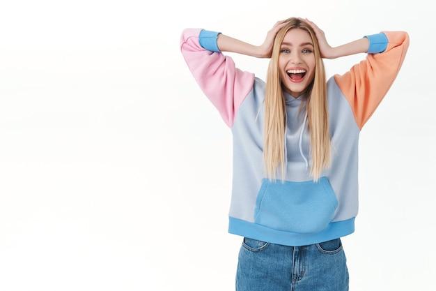 Portret wesołej, szczęśliwej kobiecej dziewczyny o blond włosach, trzymającej ręce na głowie i szeroko uśmiechającej się, wygrywającej