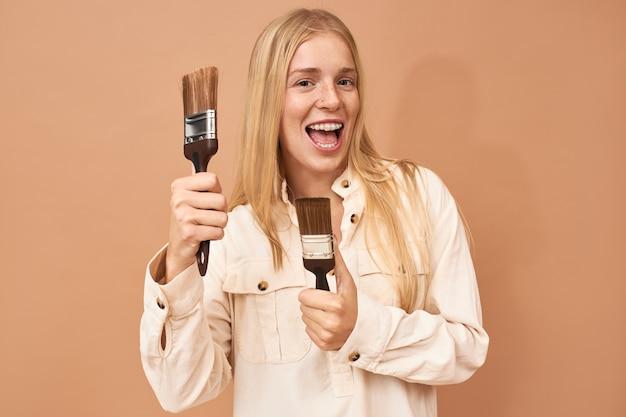 Portret wesołej, szczęśliwej młodej blondynki ze wspornikami zębów trzymającej pędzle i uśmiechającej się z podekscytowaniem, malując ściany wewnętrzne, aby poprawić wygląd swojej sypialni