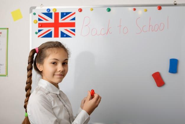 Portret wesołej uczennicy pisze na tablicy opis powrót do szkoły