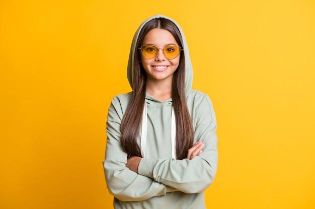 Portret wesołej uczennicy z założonymi rękami nosi okulary przeciwsłoneczne jasnozielone ubrania izolowane na żółtym tle koloru