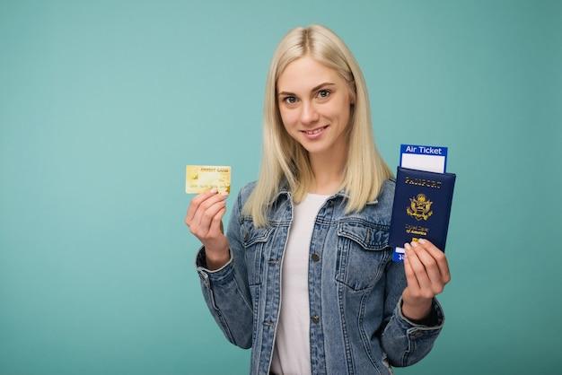 Portret wesołej, uroczej amerykańskiej dziewczyny podróżnika pokazując paszport z biletami lotniczymi i kartą kredytową