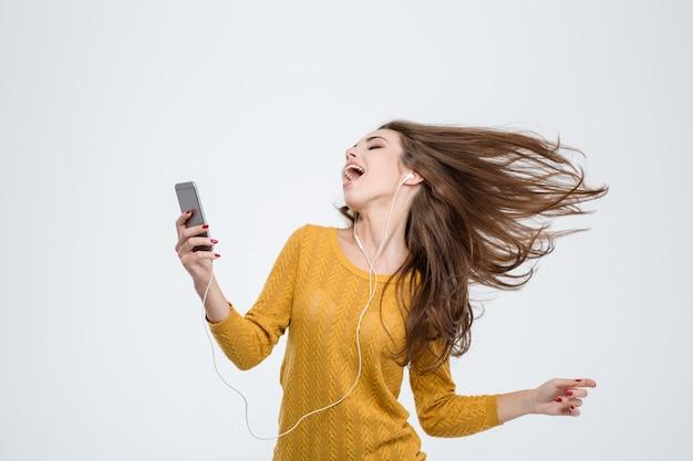 Portret wesołej uroczej kobiety słuchającej muzyki w słuchawkach i tańczącej na białym tle