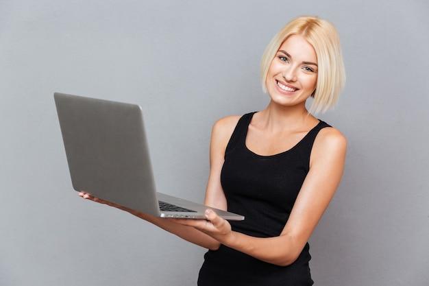 Portret wesołej uroczej młodej kobiety stojącej i używającej laptopa na szarej ścianie