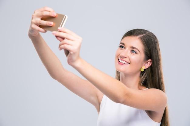 Portret wesołej uroczej nastolatka robi zdjęcie selfie na smartfonie na białym tle