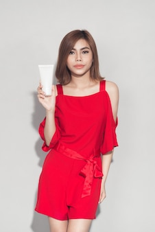 Portret wesołej uśmiechniętej dziewczyny mody w czerwonej sukience trzymającej plastikową tubkę kosmetyczną