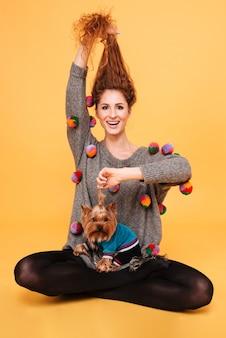 Portret wesołej uśmiechniętej kobiety z rudymi włosami bawiącej się z psem na pomarańczowej ścianie