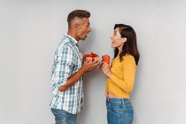 Portret wesołej uśmiechniętej, uroczej dorosłej, kochającej się pary, odizolowanej nad szarą ścianą, trzymającej dla siebie prezenty