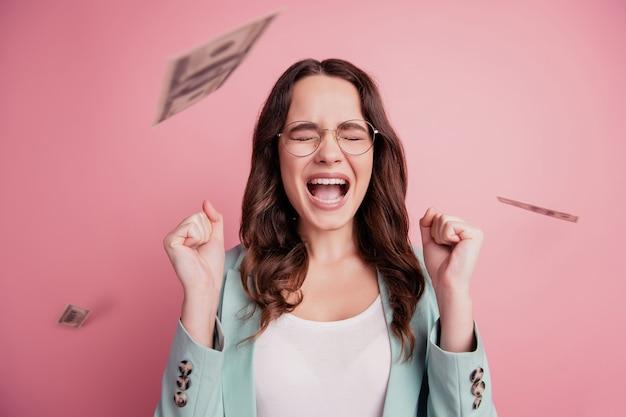 Portret wesołej zadowolonej dziewczyny cieszącej się prysznicem z dolarów