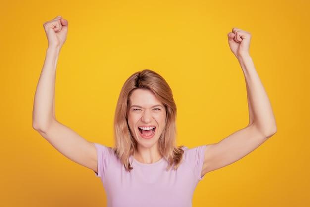 Portret wesołej zdziwionej kobiety zamykającej oczy podnoszącej ręce sceram otwarte usta na żółtym tle